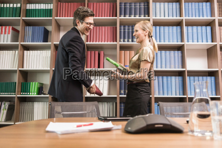 man and woman holding books laughing