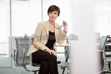 businesswoman sitting in office chair at