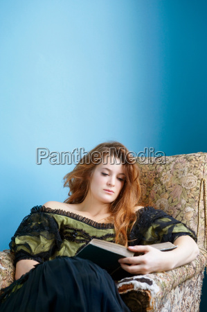 young woman on arm chair reading
