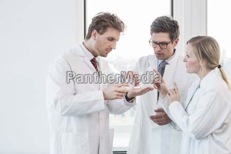 three people wearing lab coats standing