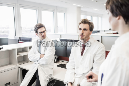 two men wearing lab coats sitting