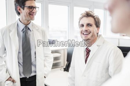 two men wearing lab coats sitting