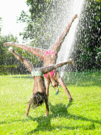 girls playing under a water jet