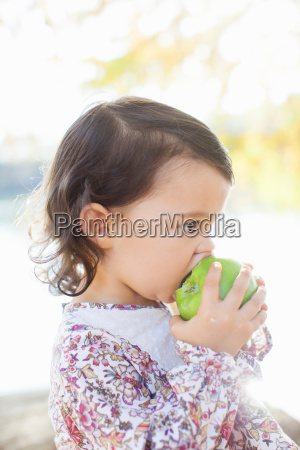 side view of child biting green