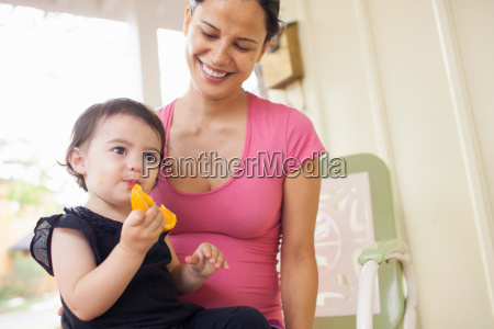 mother looking at baby girl eating
