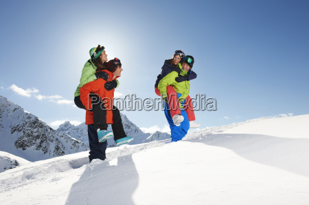 friends giving piggy backs in snow