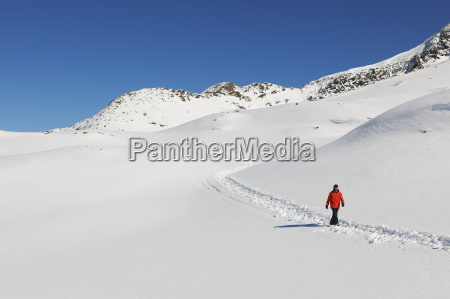man wlaking in snow kuhtai austria