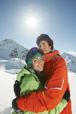 couple wearing skiwear hugging kuhtai austria