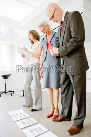 3 people inspecting papers on floor