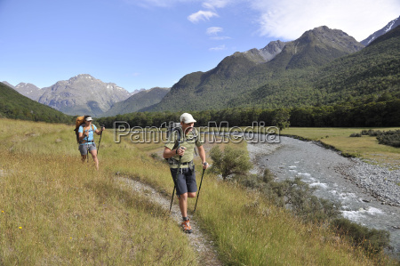 couple hiking by river new zealand