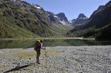woman standing by lake in mountains