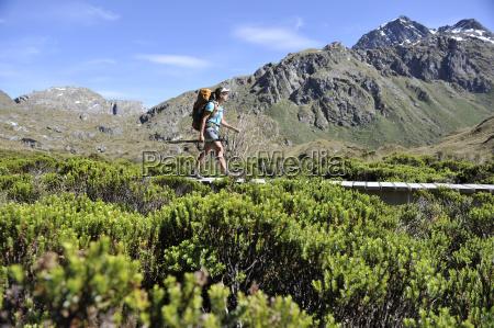 woman hiking on boardwalk new zealand