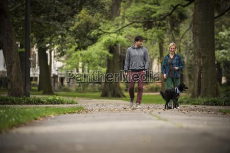 couple walking dog in park savannah