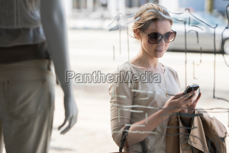 young woman checking mobile phone outside