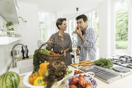 couple in kitchen preparing fresh vegetables