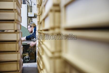 young man between stacks of letterpress