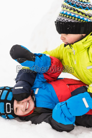 two boys play fighting in snow