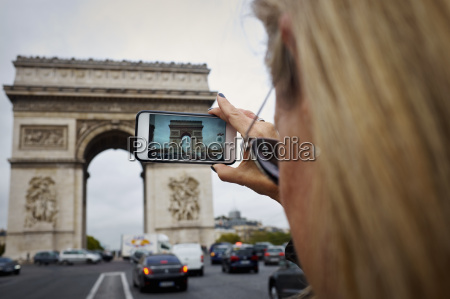 woman taking photo of the arc