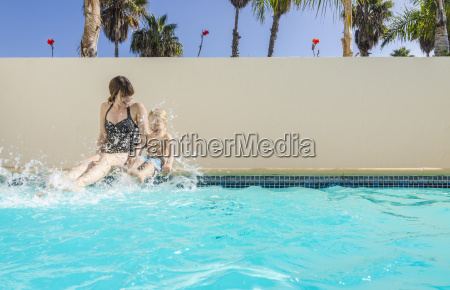 mother and son sitting splashing in