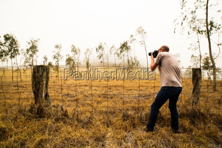 mid adult man photographing field of