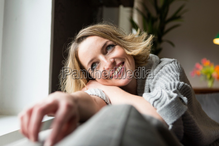 woman smiling on sofa in living