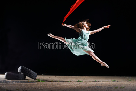 ballet dancer leaping mid air holding