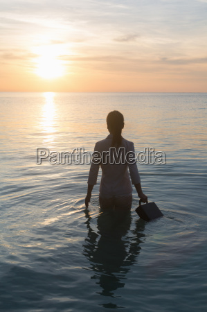 businessperson standing in sea rear view