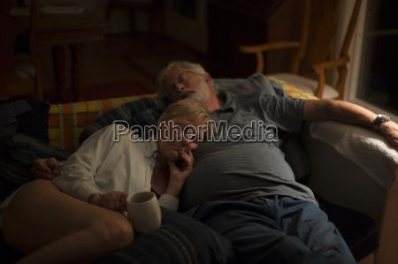 senior couple reclining on sofa at