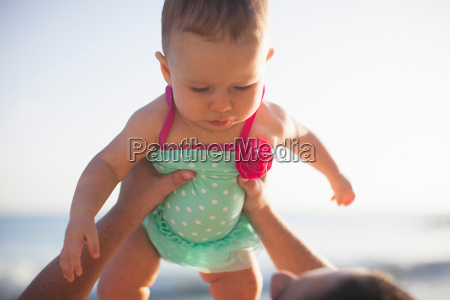 woman lifting baby girl wearing swimsuit