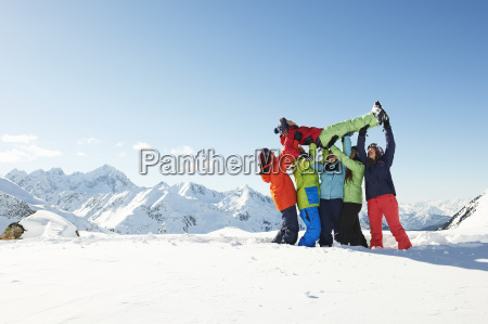 friends lifting young woman in snow