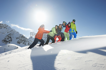 man pushing friends uphill in snow