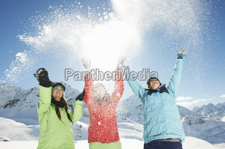 female friends throwing snow mid air
