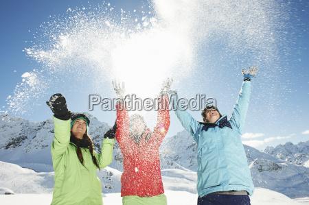 female friends throwing snow mid air