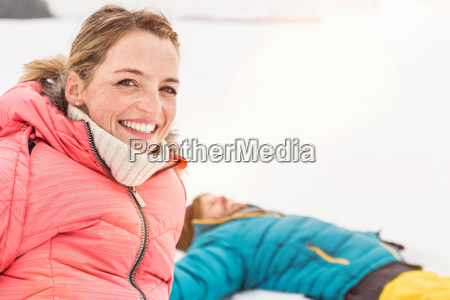 couple playing in snow woman smiling