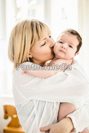 mid adult mother kissing baby boy