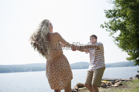 young couple holding hands by lake