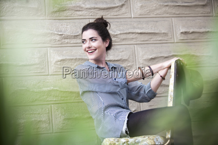 young woman sitting outside on chair