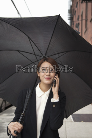 businesswoman with umbrella using smartphone on