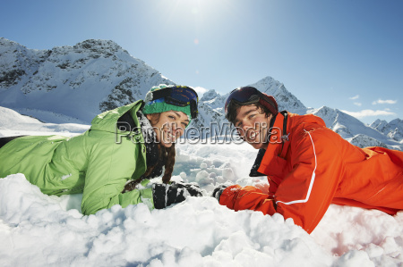 couple lying in snow kuhtai austria