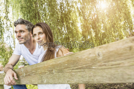 portrait of couple standing behind fence