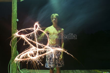 boy with sparkler at night on