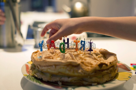 boys hand removing birthday candles from