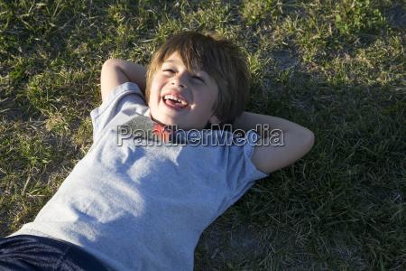 portrait of boy lying on park