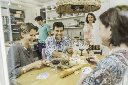 five adult friends playing cards at