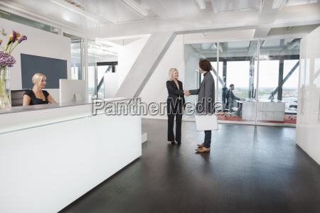 woman shaking hands with visitor at