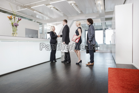 woman shaking hands with visitors at
