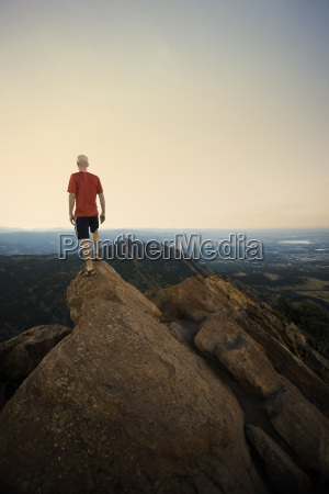 mature male hiker standing on top