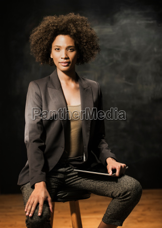 businesswoman sitting on stool with digital