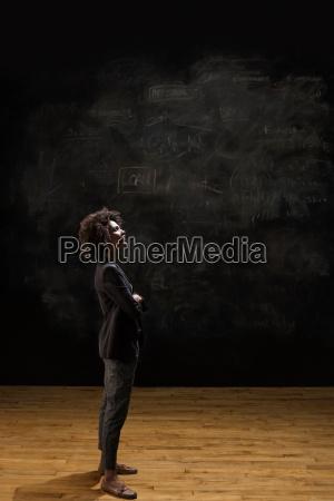 businesswoman standing by blackboard