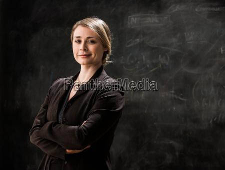 businesswoman by blackboard